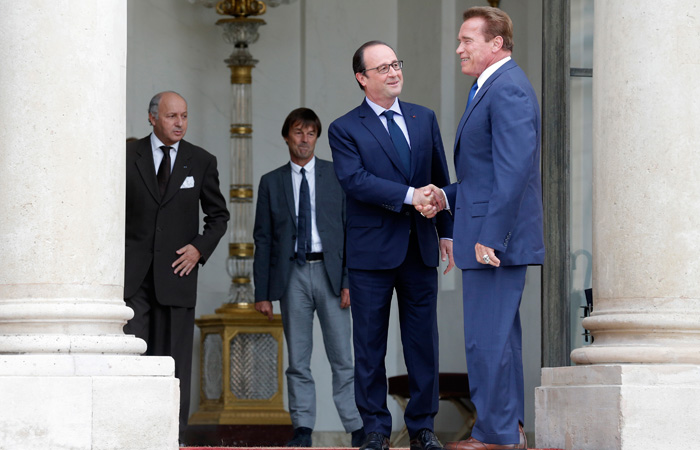 French President Hollande greets R20 founder and former California state governor Schwarzenegger, before a meeting at the Elysee Palace in Paris